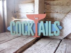 """This little fish obviously found his way to a """"bit o' the bubbly."""" Likewise, your guests will know they're in the right spot for a splash of their favorite libation when they see this fun, colorful sign. Perfect for your bar, patio, rec room, kitchen, man cave or wherever you entertain.Our artist carefully cuts all the individual pieces with a scroll saw from half inch plywood and haphazardly painted them to have a distressed """"been hanging outside on the porch for the last 40 years"""" look…"""