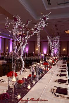 Reception table - White branches with beaded crystal accents and purple florets in large glass cylinders.