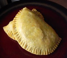 Jamaican Beef Patties Recipe Main Dishes with all-purpose flour, salt, ground turmeric, vegetable shortening, ice water, minced beef, ground allspice, ground black pepper, vegetable oil, diced onions, hot pepper, minced garlic, fresh thyme, tomato ketchup, salt, water, sliced green onions, large eggs, water