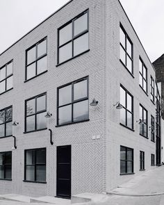 New Cross Lofts by Chan and Eayres: Pale grey bricks are arranged to create a herringbone pattern across the facade of this housing and studio block in New Cross, southeast London.