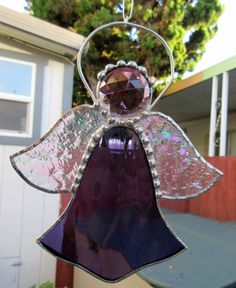 This sun catcher of an angel made of stained glass. It is purple in color, a 35 mm clear purple faceted jewel for the head, the wings are of iridescent textured clear glass and this angel is 5 inches wide by 6 inches long. It is copper foil constructed with decorative solder. To be