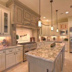 gray washed kitchen -- love the detailed cabinet above stove and countertops