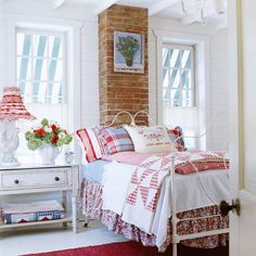 "Patriotic Palette  To achieve an all-American look, this painted iron bed is piled high with red, white, and blue linens. A floral dust ruffle lays the foundation for the color scheme, while sheets in cornflower blue and white, a red gingham comforter, a vintage quilt, and plaid and striped pillowcases continue the theme. An embroidered ""Home Sweet Home"" pillow completes the sentiment."
