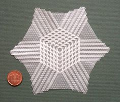 It is a nano star cube tessellation made from window glassine (35g) and folded in a 64 grid. Distance between two folds is 2 mm. It is very important to fold accurate. In the left corner is a one cent coin for comparison.