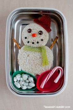 Snowman bento: Sandwich with pretzel arms, a fruit leather hat, mini m&ms for eyes, candy coated sunflower seed for a nose, smile made of black sprinkles, a licorice scarf