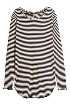 Camiseta de manga larga: Camiseta larga de punto. Mangas largas, acabados sin rematar y parte inferior redondeada.