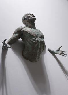 Athletic Bronze Sculptures Emerge from Walls