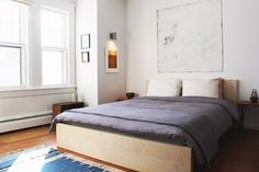 GRAY STREET GUEST HOUSE / Bedroom with mexican rug blanket, mid-century Danish night stands, repurposed nautical lamp, vintage crate bookshelf, and artwork by Antoni Ooto and Paul Douglas Olmer.