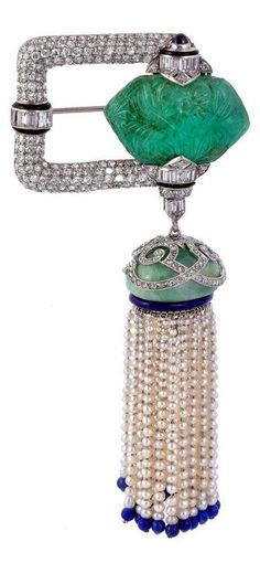 An Art Deco carved emerald, diamond, jadeite, pearl and lapis lazuli brooch, circa 1925. 10.3cm long. With French assay mark.