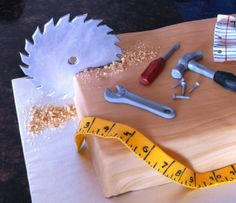 Tools for Aaron - This cake was for my good friend's son Aaron. He likes tools, even though he's not allowed to play with them. I found some great ideas on CC and sort of combined them into this cake. The tools are all handmade fondant, allowed to dry and harden. The saw dust is crumbled shortbread cookies. I used a food coloring marker to make the marks and numbers on the measuring tape.