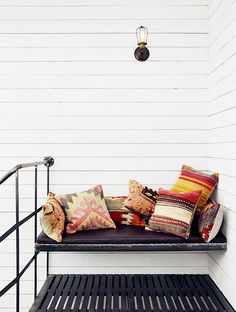 Outdoor bench seating with various patterned pillows, and industrial railing and light fixture