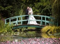 Wedding couple standing on a Monet style bridge, above lake of water lillies