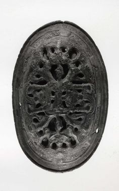 Copper alloy oval brooch: two-piece construction; openwork upper shell decorated in Borre Style animal interlace; lower shell with Jellinge Style ribbon interlace animals in panels separated by plain squares; plain flanged rim with rounded edge; round hole for chain on one side; textile impressions from casting process on back.  Gotland, 9th - 10th cent.  Photo credit - British Museum