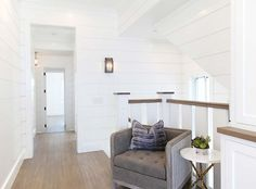 Reading Area above stairway. White shiplap walls reading area. Graystone Custom Builders.