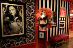 The new Victoria's Secret store . . . black & white stripes, black & white wallpaper, hot pink mouldings, black & white pictures and beautiful tufted furniture ♥
