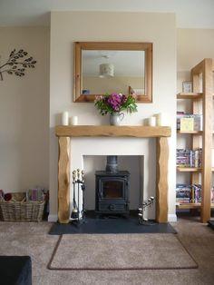 An Oak wood fireplace surround with a wood burning stove Oak Beam Fireplace, Wooden Fireplace Surround, Wooden Mantle, Stove Fireplace, Fireplace Surrounds, Fireplace Stone, Rustic Fireplaces, Oak Fire Surround, Mantle Shelf