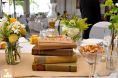 Wedding centerpieces for the nerdiest of nerds (and we absolutely love it!)... Scrabble tiles spelling the table number, placed on top of vintage books. How incredible.