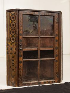 "circa 1st quarter of the 19th century, single door with six panes in original polychrome painted finish with circles, upside down pineapples and pinwheels, old ""Sotheby's Sale #5534"" printed label on top; Cupboard sold as part of the collection of Don and Faye Walters and attributed to the Mahantango Valley of Pennsylvania. Sale date 10-25-86  29 x 18 x 34.25"" high."