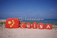 China flag and nation with the national colours on stones and beach background