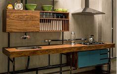 O arquiteto Kaio Chahad aproveitou a madeira do antigo forro do apartamento do fotógrafo Zee Nunes para criar a bancada desta cozinha com pegada industrial. Executado pela G Marcenaria, o móvel foi revestido com imbuia e ganhou pés de ferro fundido