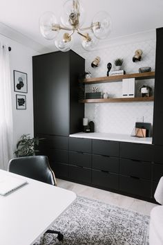 Wow! A stunning modern home office renovation reveal! This stunning space features black IKEA kungsbacka kitchen cabinets, tiled floors, a beautiful watercolour wallpaper mural, and gorgeous gold and brass light fixtures. The white desk stands out against the beautiful green mural. A stunning contemporary office for men or women. Great small office space ideas for storage and minimalist design. #office #homeoffice #moderndesign #blackcabinets #blackkitchencabinets #monochrome