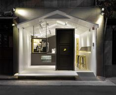 A door and deep-framed window are set into the glass house-shaped facade of this cupcake shop in Taiwan