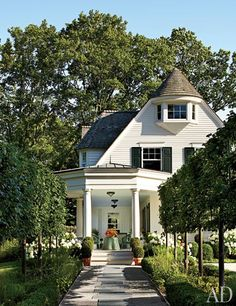 To create a stately path to the front porch, Miranda Brooks Landscape Design installed an allée of pleached lindens and boxwood hedges.