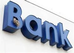 These birds are nesting int he B of the Bank sign.  Birds pick unusual places to nest, but they have to fit their homes into city living. The find a way to do this the best they can, and they are rather good at it.