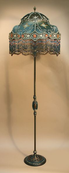 Painted metal, ornate floor lamp holds a 'WHIMSEY' shaped shade. Ombre dyed from burnt orange into deep teal blue, the shade is covered, all over, with parts of a vintage, silk, Indian SARI cloth; hand embroidered with gold metallic flourishes, leaves and sequins, orange, coral and blue flowers. Hand beaded fringe. http://www.antiqueartistry.com/floorlamps/