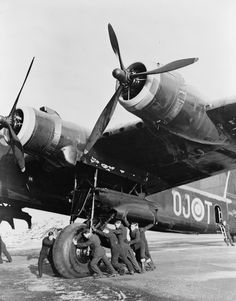 British mechanics push a Short Stirling heavy bomber off of a runway.