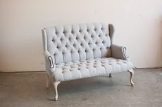 Button-tufted wingback settee from Found Vintage Rentals.