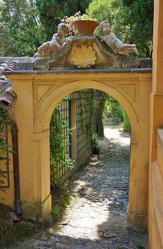 Garden arch with stone cherubs atop