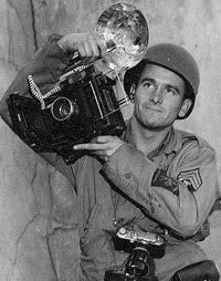 U.S. Army Signal Corps photographer Tech. Sgt. Harold Warren King with his 4x5 Anniversary Speed Graphic camera (PH-47E) and a 35mm Leica camera.