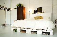 White bed on platform (pallets?) with books underneath.