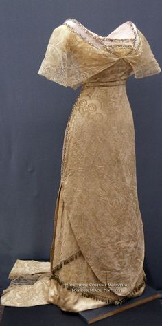 Evening dress ca. 1911-12. Cream silk damask with shoulders, sleeves, & center front neckline of silk tulle. Neckline edged in rhinestones & flounce of machine Chantilly lace. Skirt edged in small oblong metallic pom-poms and a short rectangular train made of two panels joined with machine silk chantilly. It has attached cream satin underskirt. It originates at center back [high] waistline. Private collection via Northeast Costume Mounting