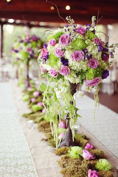 babys breath arrangment instead the flowers they've got, the moss exactly the same, book pages instead of burlap. candles in jars and cans on either side of arrangments. no table cloth.