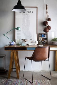 I love the sawhorse table with the narrow shelves. Great vignette, too. I love the industrial-looking clamp-on table lamp, the overhead light. And that group of gourds (I think) hanging on the wall are just the perfect balance.