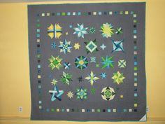 2014-2015. Back of L & T wedding quilt.  It contains 6 small stars, 13 medium stars and 15 large stars to commemorate their anniversary date - 6/13/15.  All stars were paper pieced.  My first project doing paper piecing and I enjoyed it. Made with Kona grey fabric and batik fabrics.