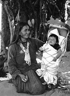 Navajo woman with papoose in cradleboard. Love the smile on her face!