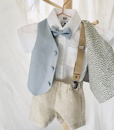 Boys summer Baptism wedding outfit with dusty blue linen vest waistcoat, beige linen shorts, white linen shirt, dusty blue bow tie Baby Boy Dress, Baby Boy Outfits, Kids Outfits, Blue Suit Shoes, Baby Boy Baptism, Baby Boys, White Suspenders, Rehearsal Dinner Outfits, Beige Vests