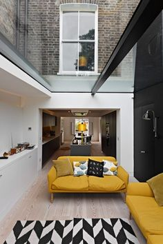 A garden-facing living space beyond features a magnificent glass roof and doors, and a slim picture window cut into a black-painted wall. The Kenneth sofas are from SCP. The Dandelion Clocks fabric on the cushions is by Sanderson, and the wall lamp (j Home Design Decor, Interior Design Inspiration, House Design, Home Decor, Design Ideas, Interior Architecture, Interior And Exterior, Yellow Interior, Yellow Sofa
