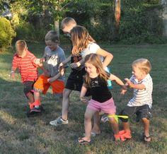 drie benen race. Parcours afgaan terwijl ze met een been aan een ander (papa of mama) zitten de snelste tijd proberen te maken. Leuk als ze bijvoorbeeld rondje om de aarde moeten lopen. Eindpunt van parcours een wereldbol.