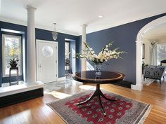 Charcoal walls white trim and red oriental rug with dark wooden accents