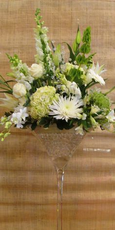 Fun party centerpieces in giant martini glasses! This one even has crystals intertwined in the green & white flowers. ~ Baltimore, MD ~  www.jandaflorist.com