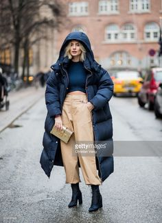 Lisa Hahnbueck wearing navy Tommy Hilfiger x Gigi Hadid down feather jacket, coat, Alexander Wang cropped top, beige I Am Gia cropped wide leg pants, Dior boots, golden Louis Vuitton petite Malle bag is seen during the Copenhagen Fashion Week Autumn/Winter 18 on February 2, 2018 in Copenhagen, Denmark.