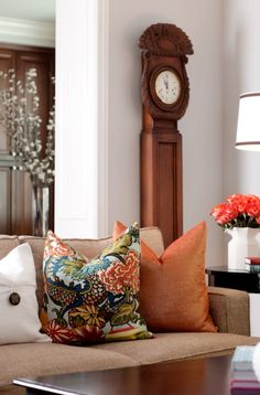 Gorgeous living room design with brown linen sofa, orange organza pillow, Chiang Mai Dragon aquamarine fabric pillow, gray blue walls paint color and grandfather clock.