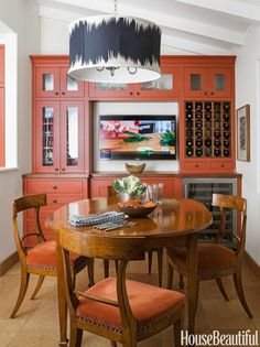 "The custom light fixture is almost as large as the breakfast table. ""With the high ceiling, I had enough space, and the Clarence House fabric I used for the shade — Operato — needed that scale,"" says designer Melanie Coddington. Orange Cabinets, Orange Kitchen Cupboards, Kitchen Redo, Kitchen Design, Burnt Orange Kitchen, Home Kitchens, Dream Kitchens, Interiores Design, Beautiful Homes"