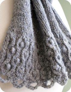 Ein üppiger und eleganter Schal präsentiert ein einfaches verdreht Kabel zu nähen und Bommel-Gestaltung. Fertig sind die Seiten mit einem i-Schnur