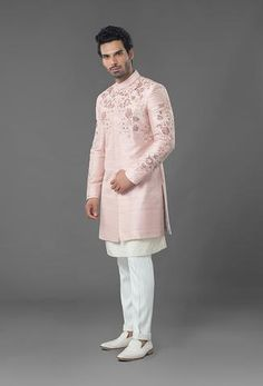 Sherwani is featured in light pink colour in raw silk fabric with dull gold zari and white thread embroidery. Kurta and Trouser are featured in ivory color. Sherwani For Men Wedding, Wedding Dresses Men Indian, Sherwani Groom, Wedding Dress Men, Wedding Suits, Indian Dresses, Mens Indian Wear, Mens Ethnic Wear, Indian Groom Wear