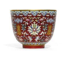 A FAMILLE-ROSE RUBY-GROUND 'LOTUS' CUP DAOGUANG SEAL MARK AND PERIOD the deep U-shaped body rising from a short straight foot, brightly enamelled and gilt around the exterior with lotus strapwork divided by shou characters, all within lotus and ruyi bands and reserved on a rich ruby-red ground, the interior glazed turquoise, the base inscribed with the iron-red seal mark